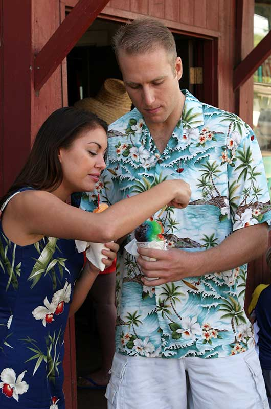 sharing shave ice in a scenic Hawaiian shirt