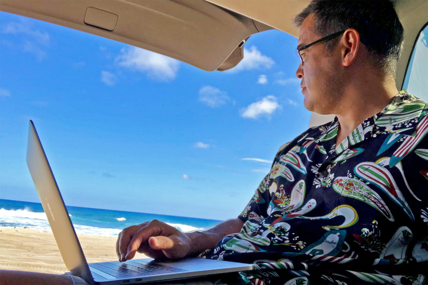 telecomuting on a laptop in the back of an SUV on the beach in a Hawaiian shirt