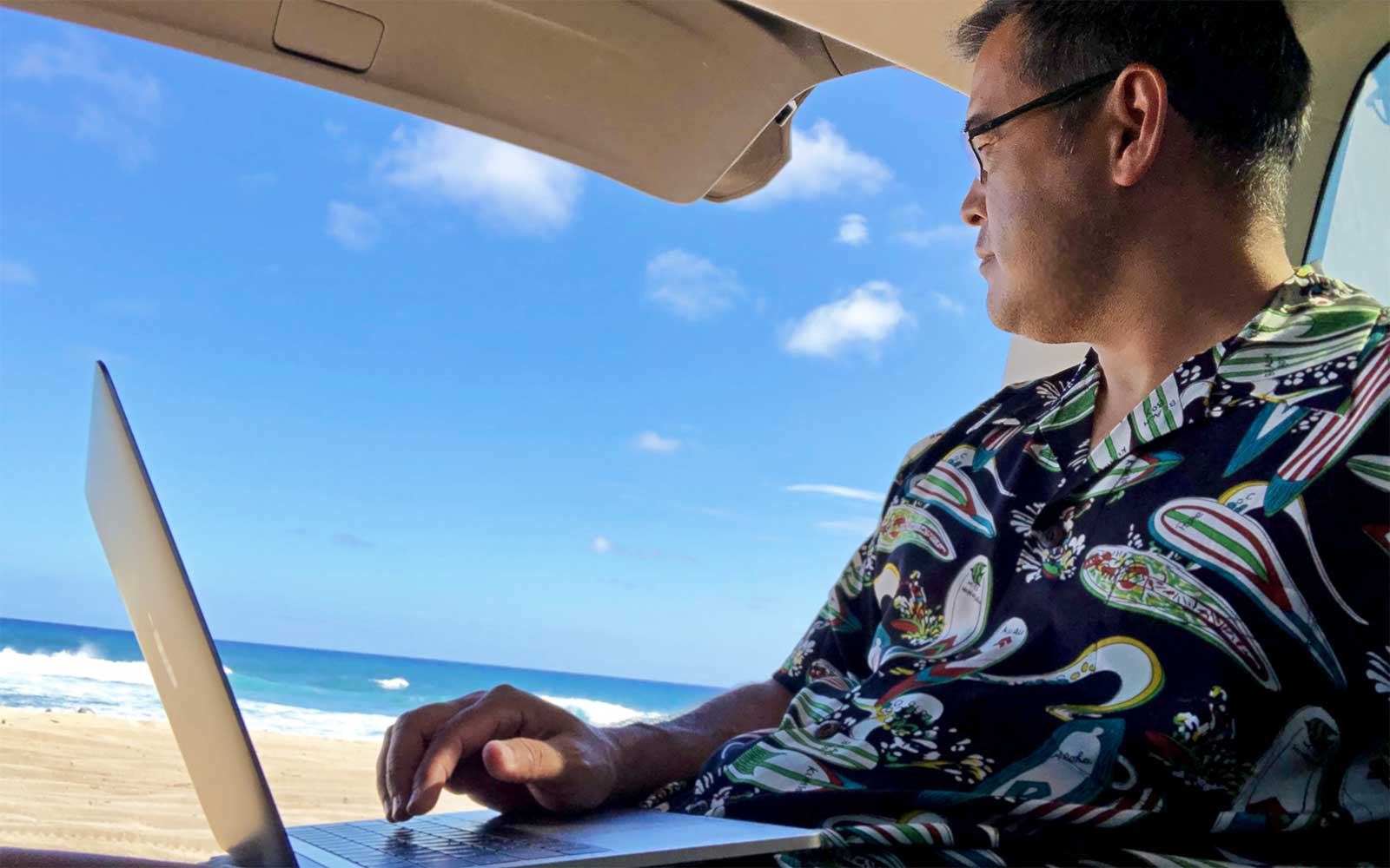 wearing a retro Hawaiian shirt while working out of the back of an SUV on the beach