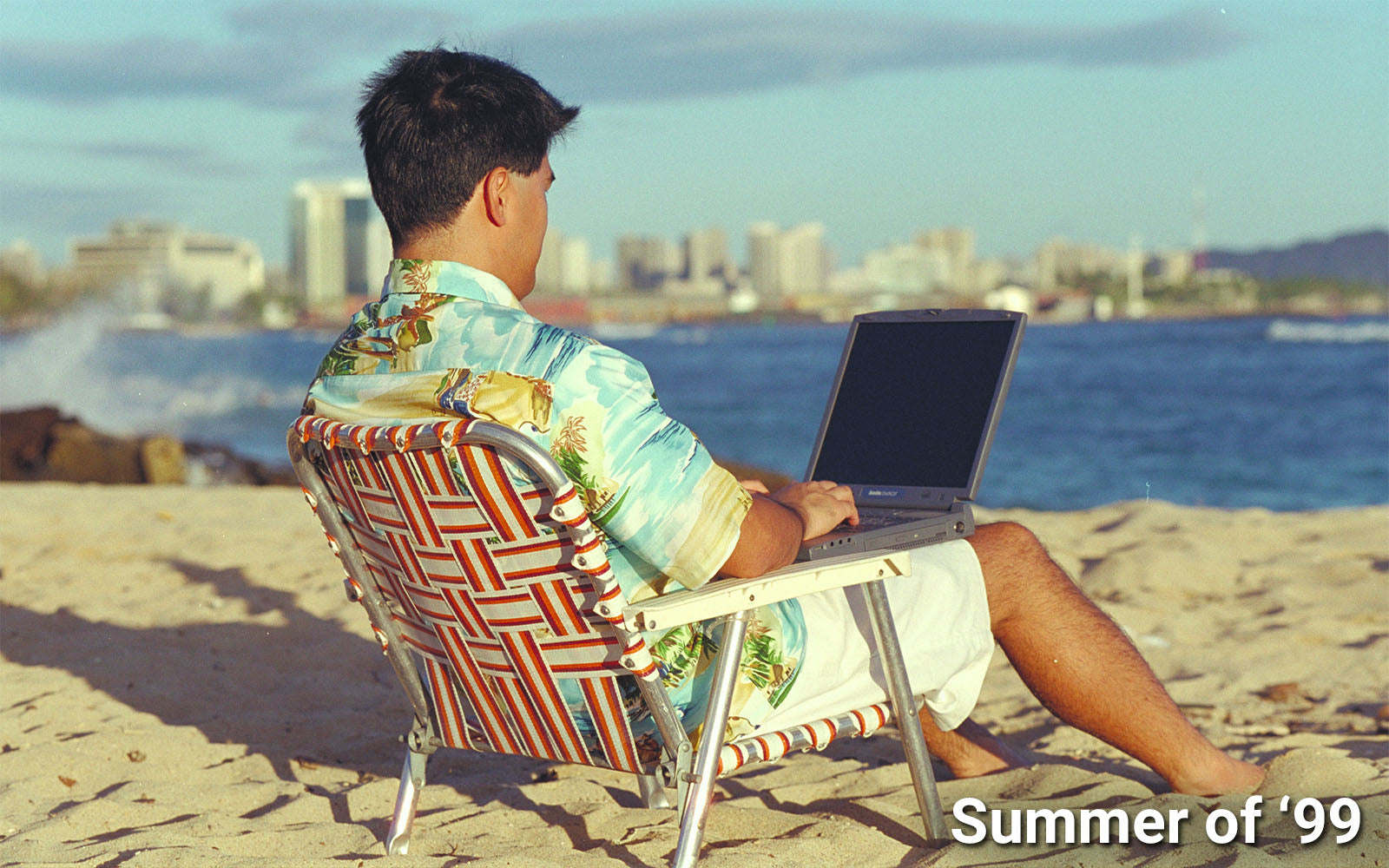 working on the beach in an Aloha shirt