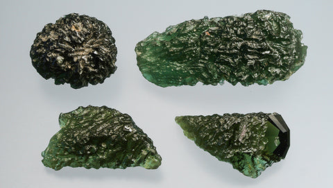 ic:Two moldavites from southern Bohemia, Czech Republic (top row) and two recent imitations from China (bottom row). The natural specimen on the top right measures 44 mm across. Photo by Jaroslav Hyršl