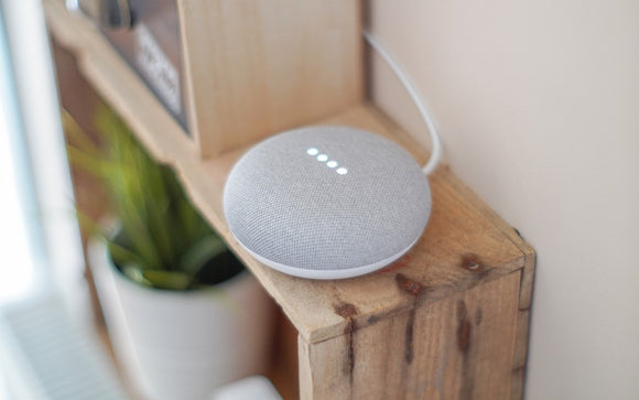 Google Home Mini Speaker on a Bookshelf