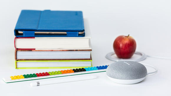 Google Home Mini beside textbooks and apple