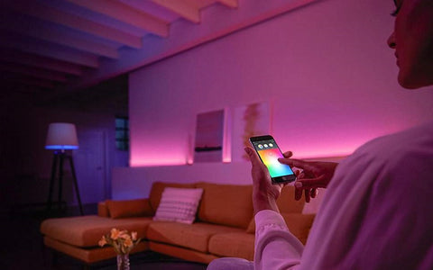 Woman controlling smart lighting from smartphone app