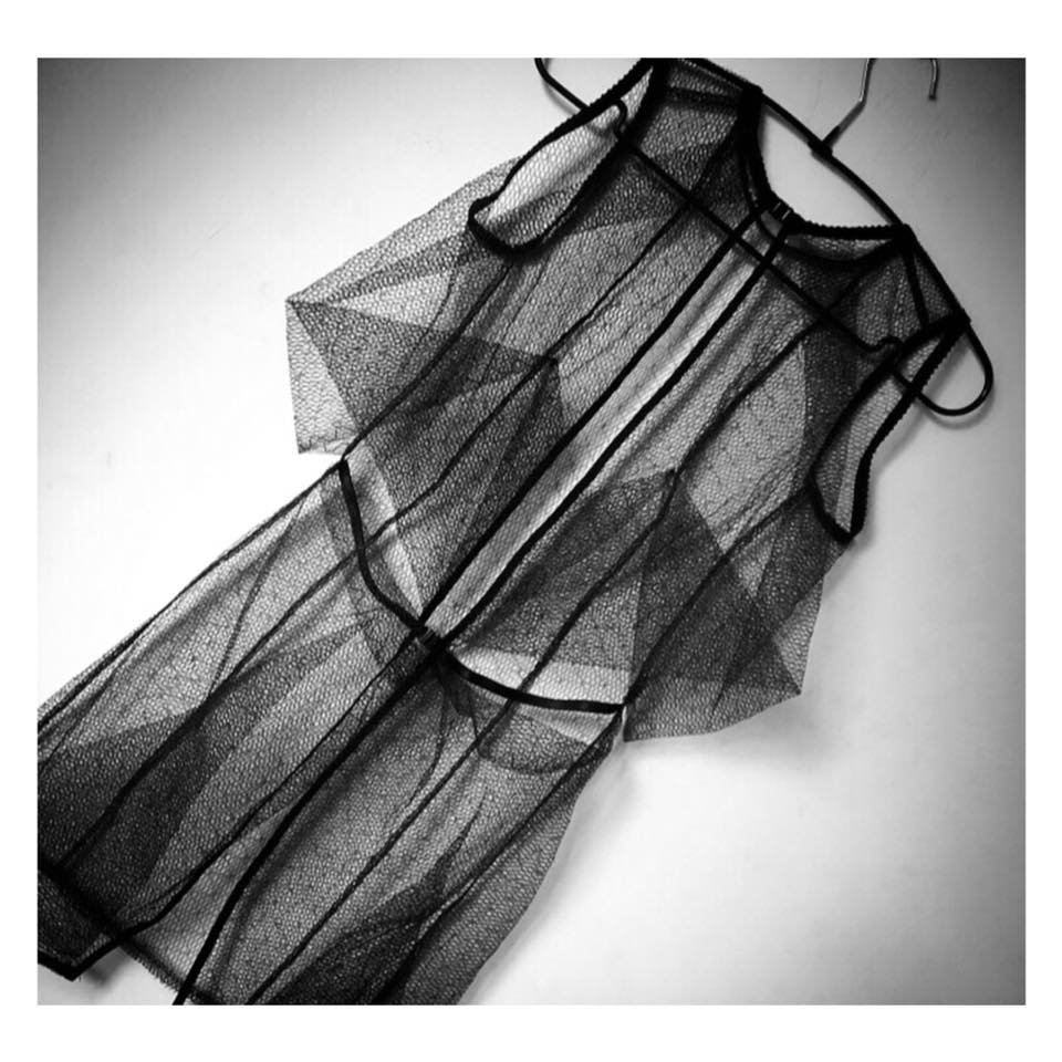 Sleeveless short origami square detail in back  black tulle dress with streamlined simple front .