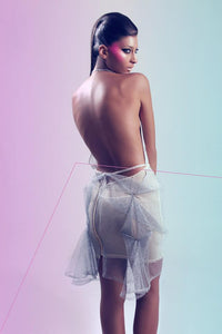 Silver tulle origami folded skirt in shapes of triangles over nude colored fabric base .