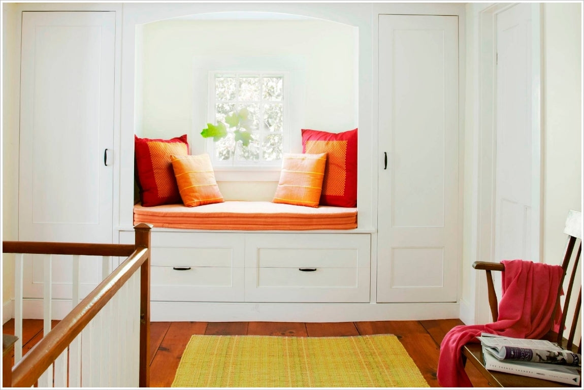 a window seat with tower like cabinets and drawers