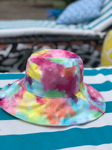 "1980s/90s bucket hat fashion trend. Featuring a tie-dyed pattern on structured vinyl body, this is an oversized bucket hat with a 3 3/4"" brim"