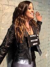 A one of a kind fringe jacket that is made out of buttery soft black faux leather and accessorized with silver and gold colored studs  and western inspired fringe trimming at sleeves and back.