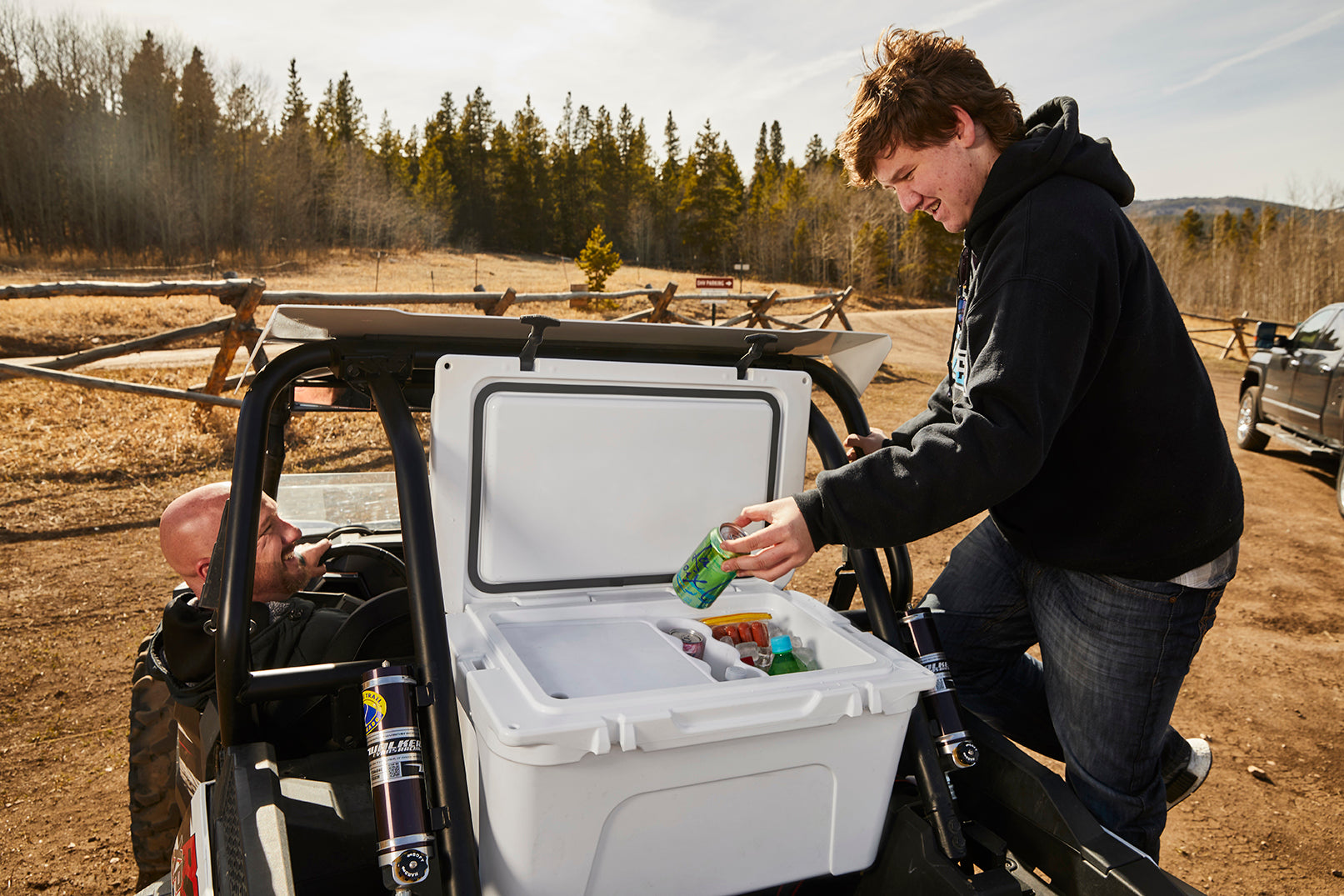 Founder Gene Perkins and son Caden pack a cooler on the back of an ATV