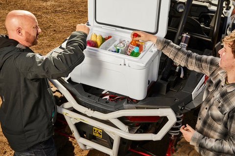 Gene and Caden packing a cooler on the back of a RZR.