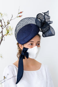 white silk face mask and navy hat
