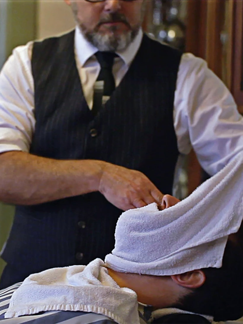 Barber holding towel over man's face