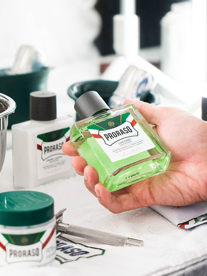Hand holding Proraso After Shave Balm Refresh formula