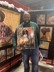Phillip Dewayne of Phillip Ashley Chocolates showing off his art prints created by artist Diedria Pigues at the Black Christmas Expo in Memphis Tn