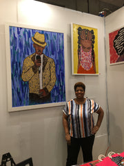 Artist Diedria Pigues standing by her artwork on display at the Harlem Fine Arts Show