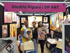Diedria Pigues standing with clients holding merchandise at the Essence festival 2019