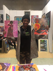 African American female holding purchased art prints created by artist Diedria Pigues at the Harlem fine arts show