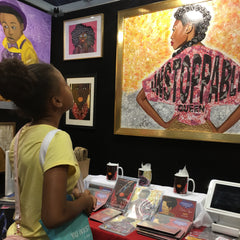 Diedria Pigues watching a little black girl looking up at her artwork unstoppable queen at the Essence festival 2019