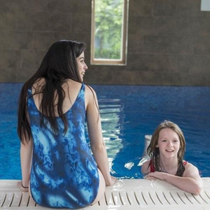 2 young teenage girls wearing the HiLINE Girls Incontinence Swimsuit in a swimming pool, swimwear, for disabled children.