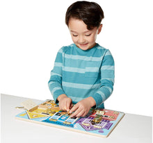 Boy playing with Latches Board, early development, for children with disabilities.