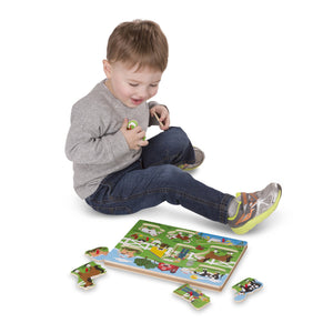 Boy playing with Old MacDonald's Farm Sound Puzzle, motor and cognitive skills, for disabled children.