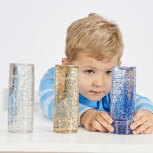 Load image into Gallery viewer, Boy playing with Sensory Glitter Storm Cylinder Toy, Learning resources, for disabled children.