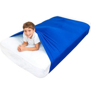 Boy smiling lying on his front with his body out of the sensory compression body sock blue, Sensory Bedding for disabled children.