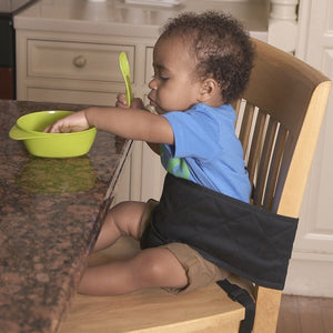 Baby sitting in Dining Chair Harness, Care & safety, for disabled children.