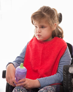 Girl in wheelchair wearing red Feeding Apron, Protective bib, for disabled children.