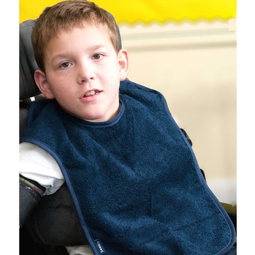 Boy in wheelchair wearing Navy Herd Apron, Protective bib, for disabled children.
