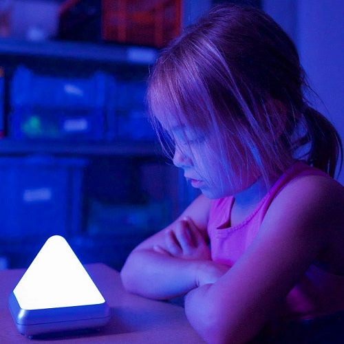 Girl looking fascinated by the colours of the Nature Sound Pyramid, motor and cognitive skills, for children with disabilities.