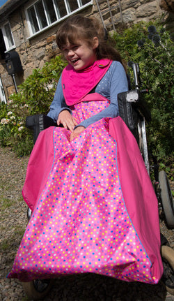 Girl using Waterproof Wheelchair Leg Cover - Pink Spot, wheelchair clothing, for children with disabilities.