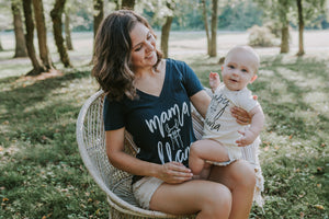 Mother sitting in a chair holding her baby wearing matching mama llama and baby llama shirts
