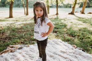 Toddler girl with her hands on her hips wearing an August Mamas Future World Changer tee
