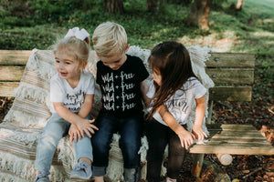 Two toddler girls and one boy sitting on park bench in their August Mamas organic cotton t-shirts