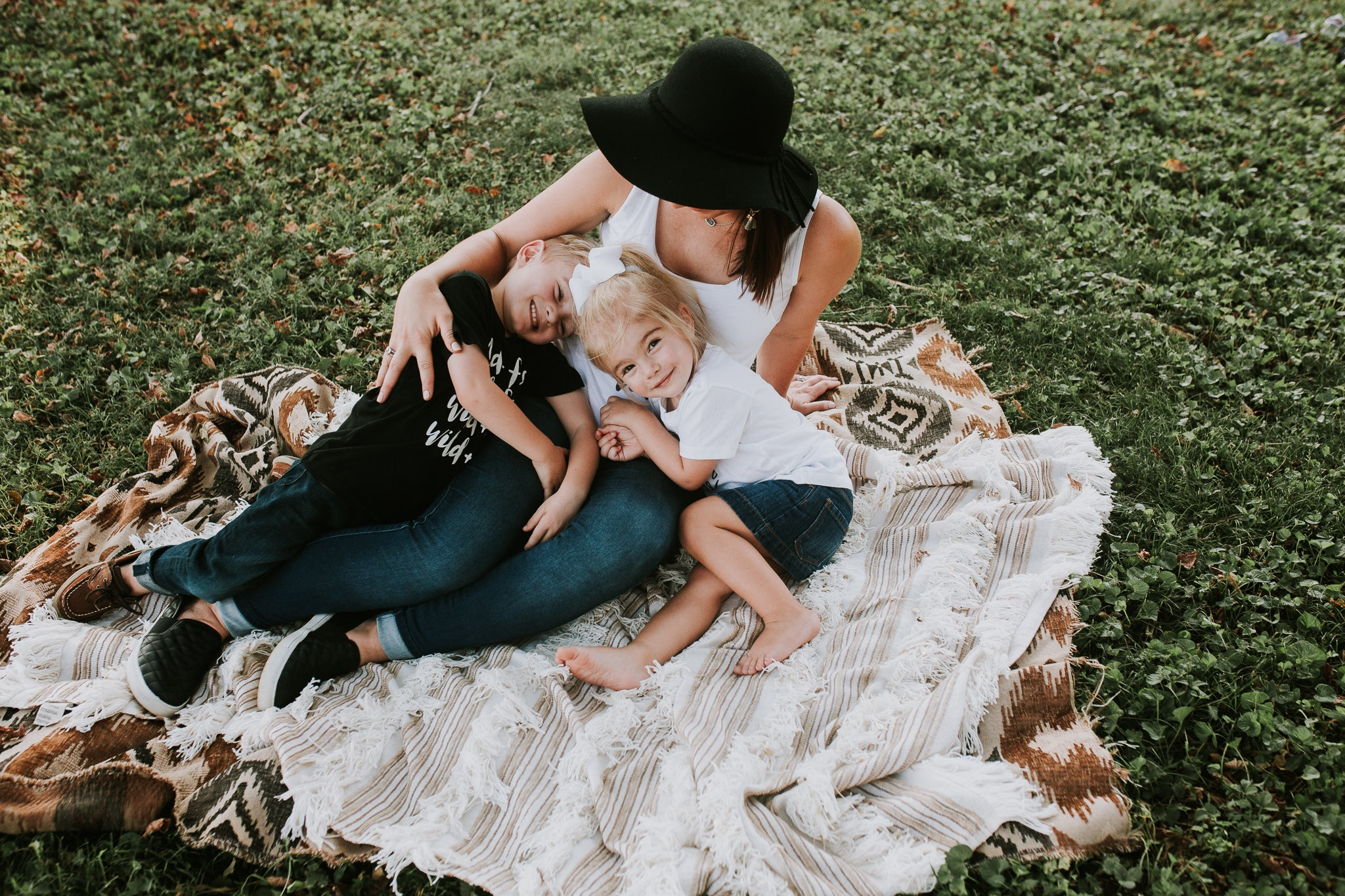 Woman and her two children sitting on a blanket outside wearing their August Mamas tees