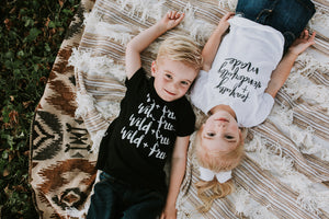 Blonde brother and sister laying on a blanket looking up wearing August Mamas t shirts