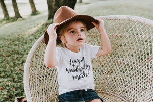 Toddler girl sitting in chair wearing a August Mamas Fearfully and Wonderfully Made t-shirt