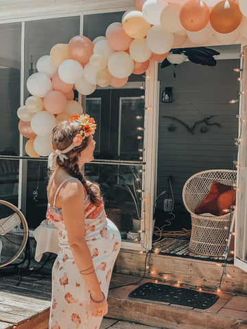 Pregnant woman looking at balloon arch at her outdoor baby shower during Covid-19