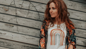 Red headed woman wearing a rainbow tee to bring awareness to miscarriage