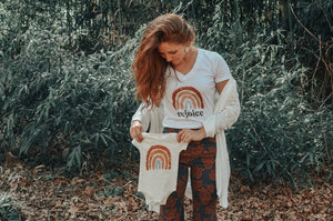 Woman wearing a rejoice rainbow white tee holding a rainbow baby onesie to honor miscarriage