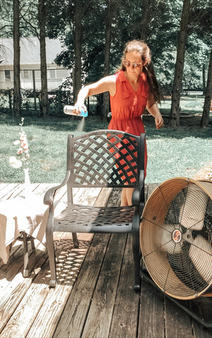 Woman spraying lysol on outdoor chairs at a Covid-19 baby shower