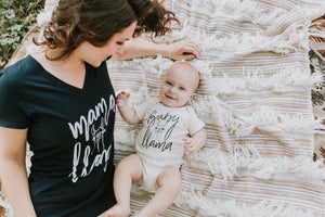 Brunette Woman Wearing a Mama Llama Hemp V-Neck Navy Blue T-Shirt, Leaning Over Her Baby Wearing a Baby Llama Onesie