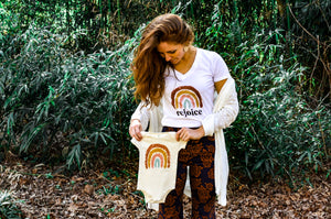 Red-headed Woman Wearing a Rainbow Rejoice Tee Holding a Cream Rainbow Onesie
