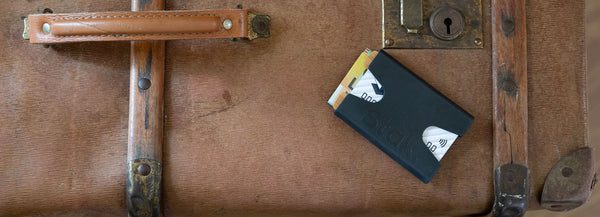 Black and Bamboo STAK Wallet on a suitcase.