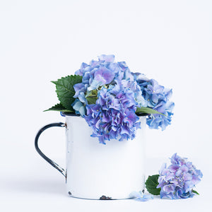 styled stock photo of blue hydrangea flowers in a rustic white mug