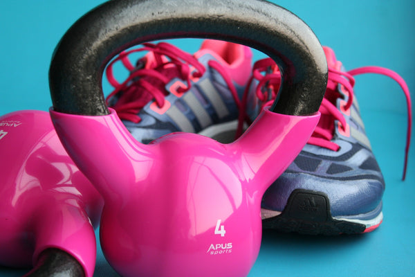 Pink gym kettlebell with shoes behind