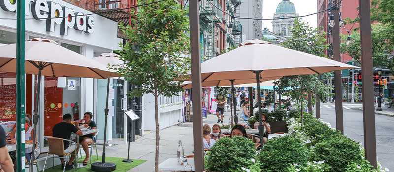 An image showing tables, flowers, and plants in the corner layout of Viida' Jardin/SoHo street patio in New York.
