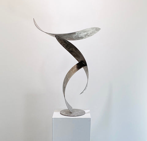 Metal sculpture placed on a white pedestal in front of a white wall.